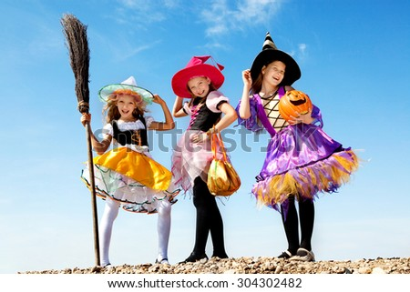 Three Beautiful Smiling Little Girls with Long Hair in the Colorful Witch Costume Looking at Camera with Broom and Trick or Treat Bags. - stock photo