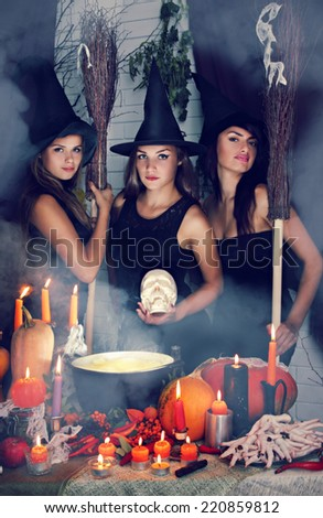 three beautiful witch with a skull and brooms - stock photo