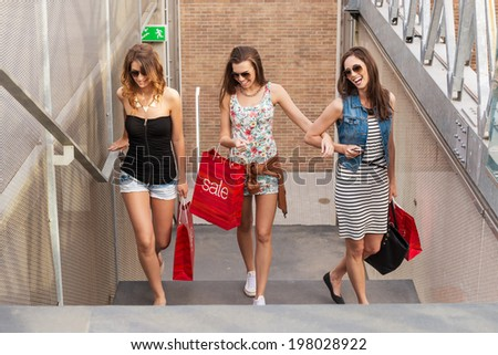 Three beautiful woman walks up the stairs, they go shopping  - stock photo
