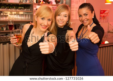 Three beautiful women drinking and celebrating in a bar as they show thumbs up into the camera - stock photo