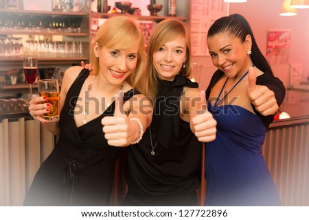 Three beautiful women drinking and celebrating in a bar as they show thumbs up into the camera with white vignette - stock photo