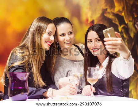 Three beautiful women having fun in a wine bar - stock photo