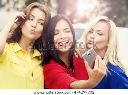 Three beautiful women taking selfies with a smartphone. Outdoor photo of a happy friends.