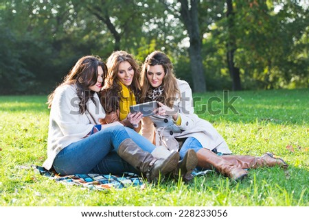 Three beautiful women using a tablet in the park - stock photo