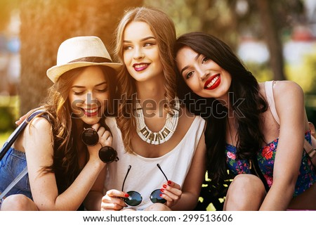 Three beautiful young girls posing against the backdrop of the park - stock photo