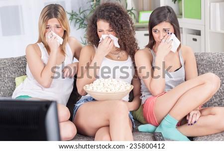 three beautiful young girls  watching sad movie depressed  - stock photo