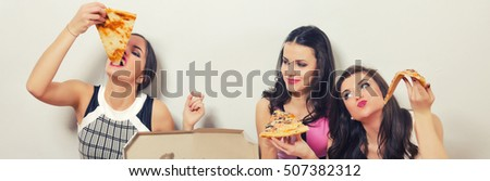 Three beautiful young ladies eating pizza while sitting on the floor.