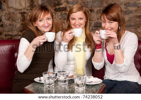 Three beautiful young students waiting drinking  coffee and having a debate in coffee shop - stock photo