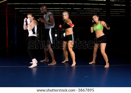 Three beautiful young woman fighters shadow boxing with their trainer in an MMA gym - stock photo