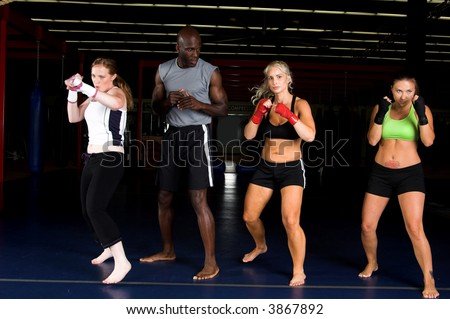 Three beautiful young woman fighters working with their trainer in an MMA gym - stock photo