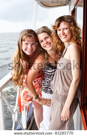 Three beautiful young women a Caucasians standing together on the deck of yacht in cruise