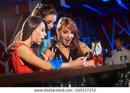 Three beautiful young women friends having fun looking at something funny on their smart phone and laughing