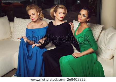 Three beautiful young women in evening gowns sitting on creamy sofa - stock photo