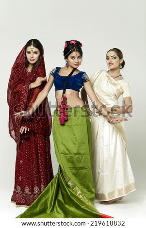 Three beautiful young women in indian dress on gray background - stock photo