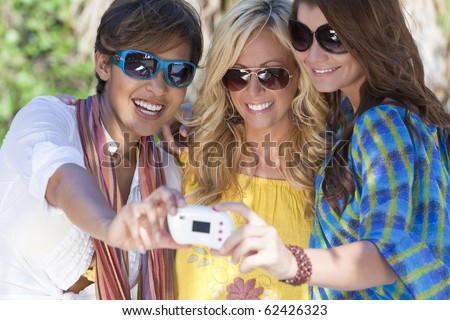 Three beautiful young women in their twenties laughing and having fun taking pictures of themselves using a digital camera while on vacation in a tropical resort location. - stock photo