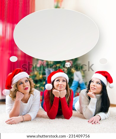 Three beautiful young women lying in front of a Christmas tree with think bubble