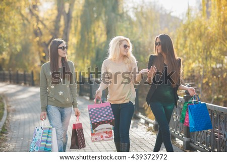 Three Beautiful Young Women with Shopping Bags. Happy shopping woman with a group of friends at the background - stock photo