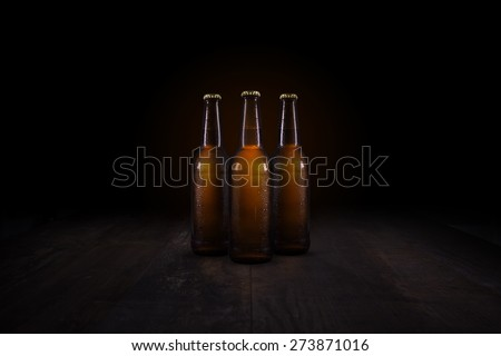 Three beer bottles standing on a rustic wooden table - stock photo