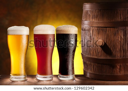 Three beer glasses with a wooden barrel. Background - dark yellow gradient. - stock photo