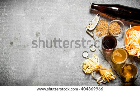 Three beers on a stone pedestal and salty cheese for beer. Free space for text. Top view - stock photo