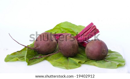 Three beetroots and their leaves isolated on white background
