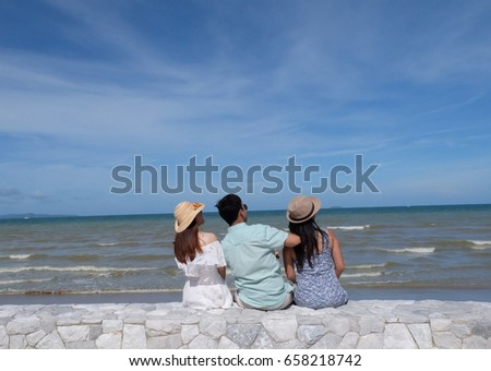 Three best friends look over the sky and think about the future so soon with a fresh air and wave sound surrounded on the beach