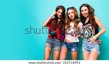 Three best friends posing in studio, wearing summer style outfit and jeans shorts  against blue background. Girls smiling and having fun. - stock photo