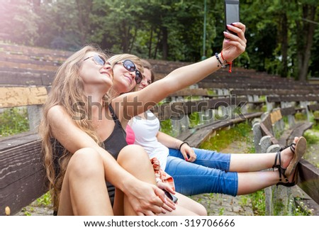 Three best friends taking a selfie outdoors - stock photo