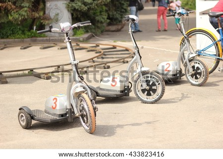 Three bicycle scooter stand in the middle of the street. - stock photo