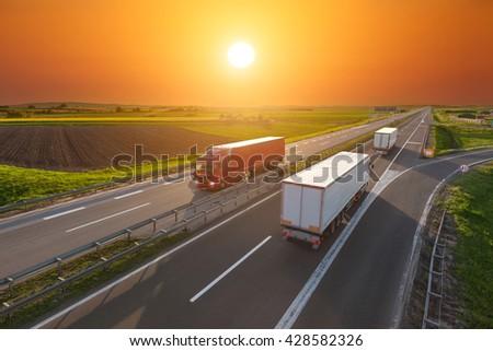 Three big trucks driving towards the sun. Fast blurred motion drive on the freeway at beautiful sunset. Freight scene on the motorway near Belgrade, Serbia. - stock photo