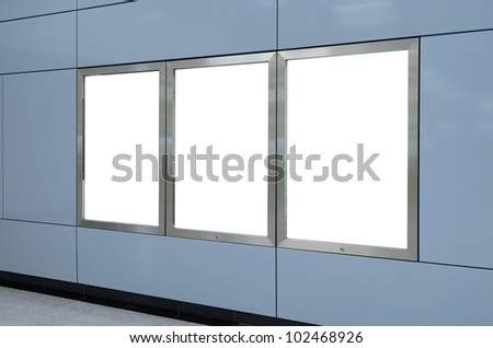 Three big vertical / portrait orientation blank billboard on modern blue wall - stock photo