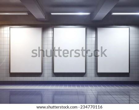 three big vertical poster on metro station - stock photo
