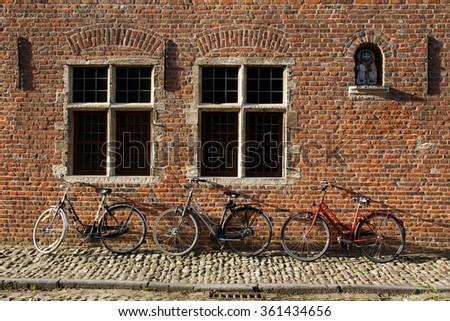Three bikes parked against renaissance house, Louvain, Belgium - stock photo