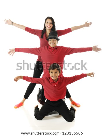 """Three biracial siblings stacked behind each other with their arms outstretched, like a 3-headed bug with 6 """"legs."""" - stock photo"""
