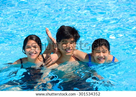 Three biracial teen siblings smiling together in pool  - stock photo