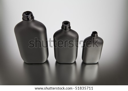Three black bottles on shinny background, reflection - stock photo