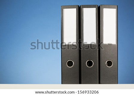 Three black business folders with blue background.