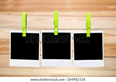 Three black instant photo, hanging on the clothesline on wooden background. - stock photo