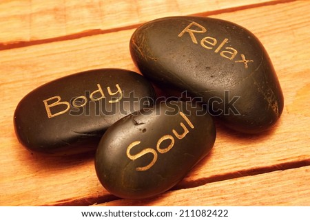 Three black lava stones with highlights on wooden board - stock photo