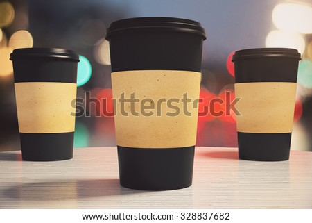 three black paper coffee cup on a table in a cafe, mock up - stock photo