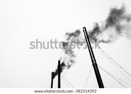 Three black pipe and black smoke on a light gray background of the sky.  - stock photo