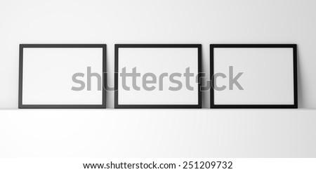 three blank black photo frames on white shelf - stock photo