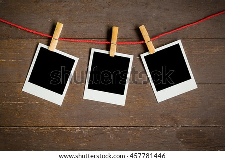 three blank photo frame hanging on wood background with space