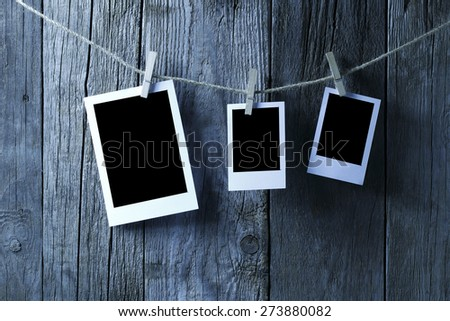 Three Blank photographs hanging on a clothesline,blue tone. - stock photo