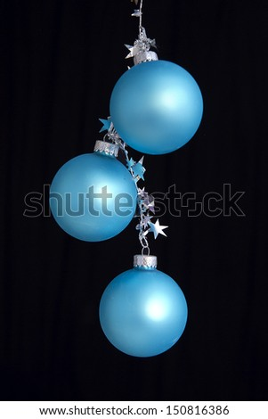 Three blue christmas ornaments hanging by silver star shaped garland - stock photo