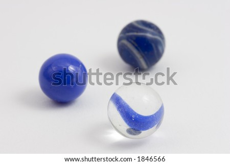 Three blue marbles with shallow depth of field. - stock photo