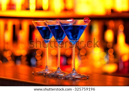 Three Blue Martini cocktails shot on a bar in dim warm light.