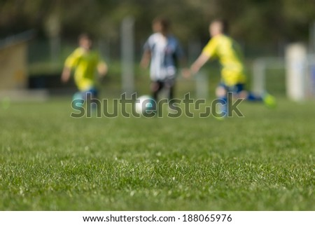 Three blurred soccer players on a soccer pitch. - stock photo