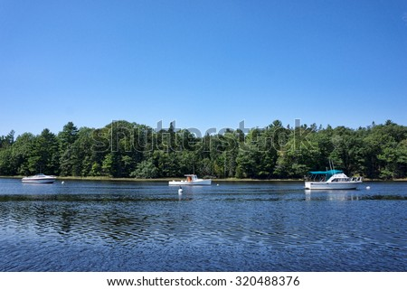 Three boats moored on Union River at Ellsworth Maine in the summertime. - stock photo