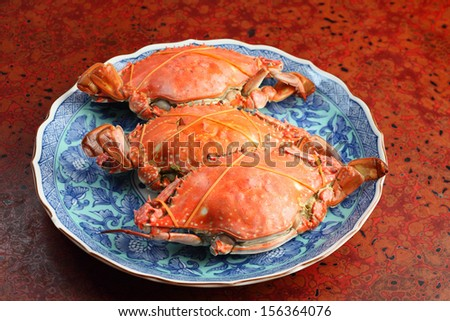Three boiled crabs prepared on plate - stock photo
